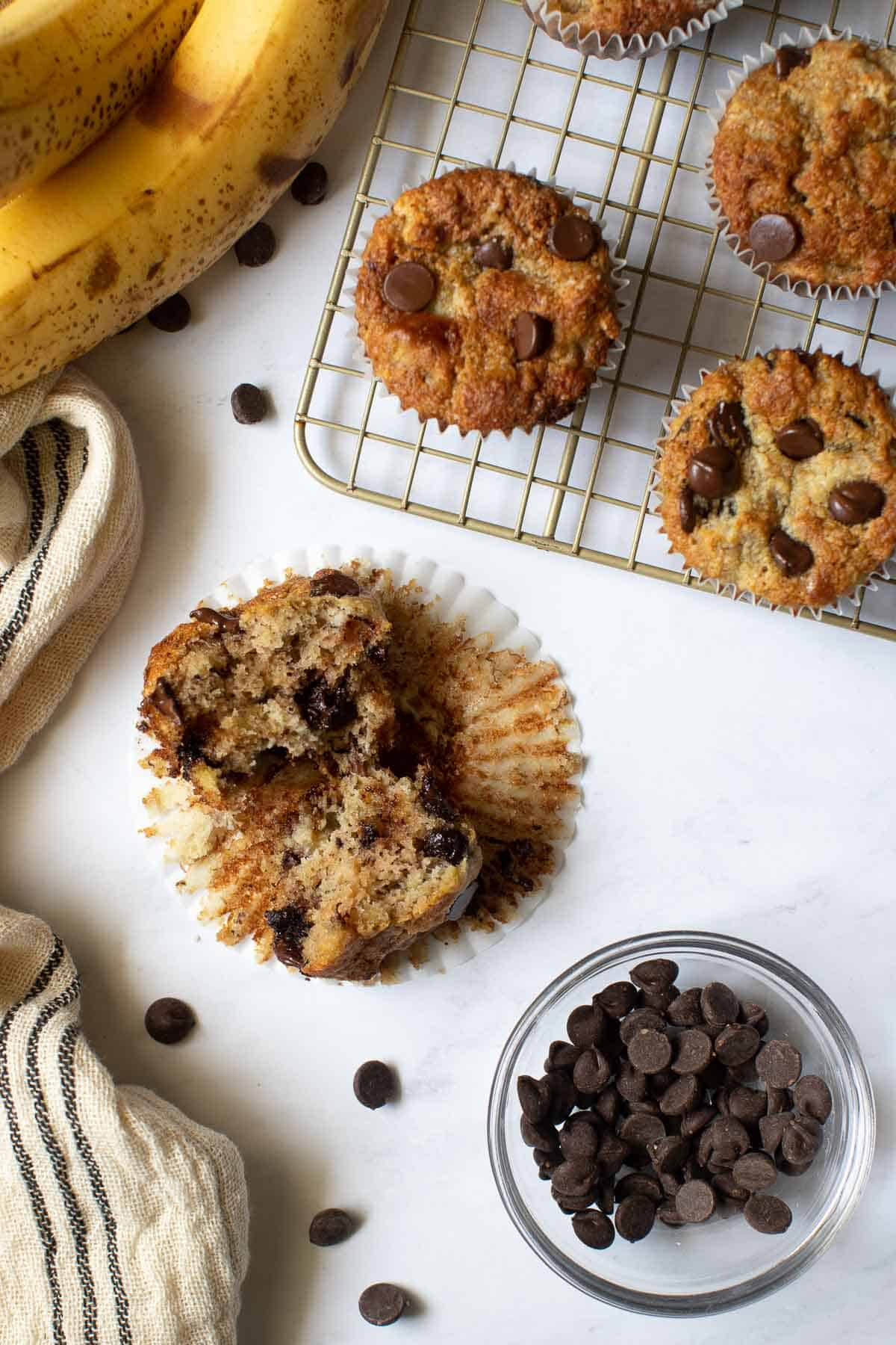 Banana muffin split open with bowl of chocolate chips on the side.