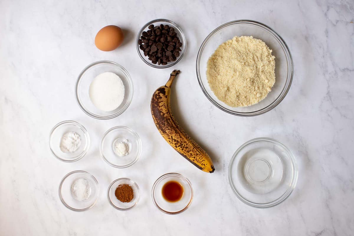 Ingredients for almond flour banana muffins on marble table.
