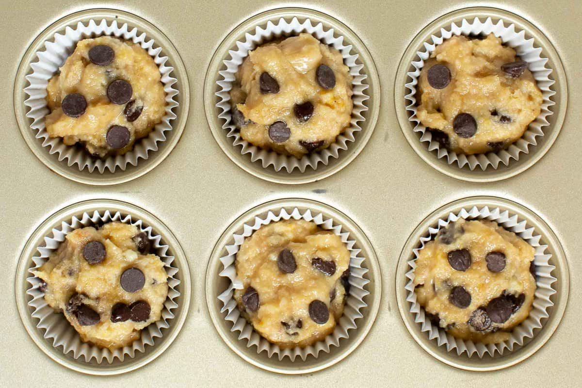 Raw banana chocolate chip muffins in muffin pan with liners.