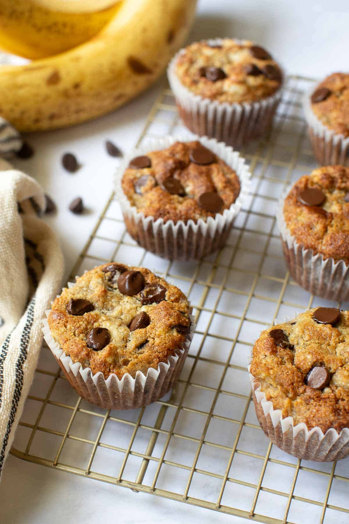 Six almond flour banana muffins with chocolate chips on wire rack.