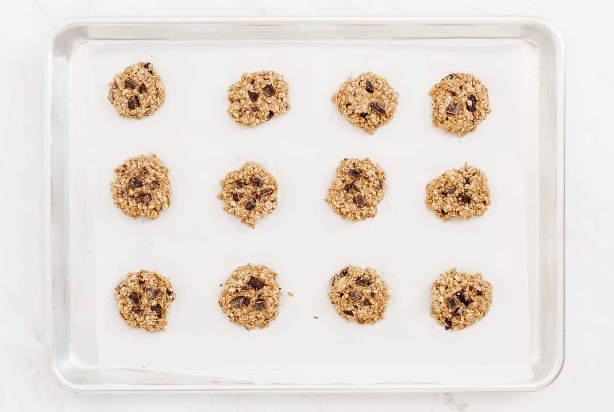 One dozen oatmeal cookie scooped onto cookie tray with parchment.