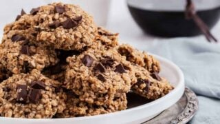 Pile of oatmeal cookies with chocolate chips on plate.