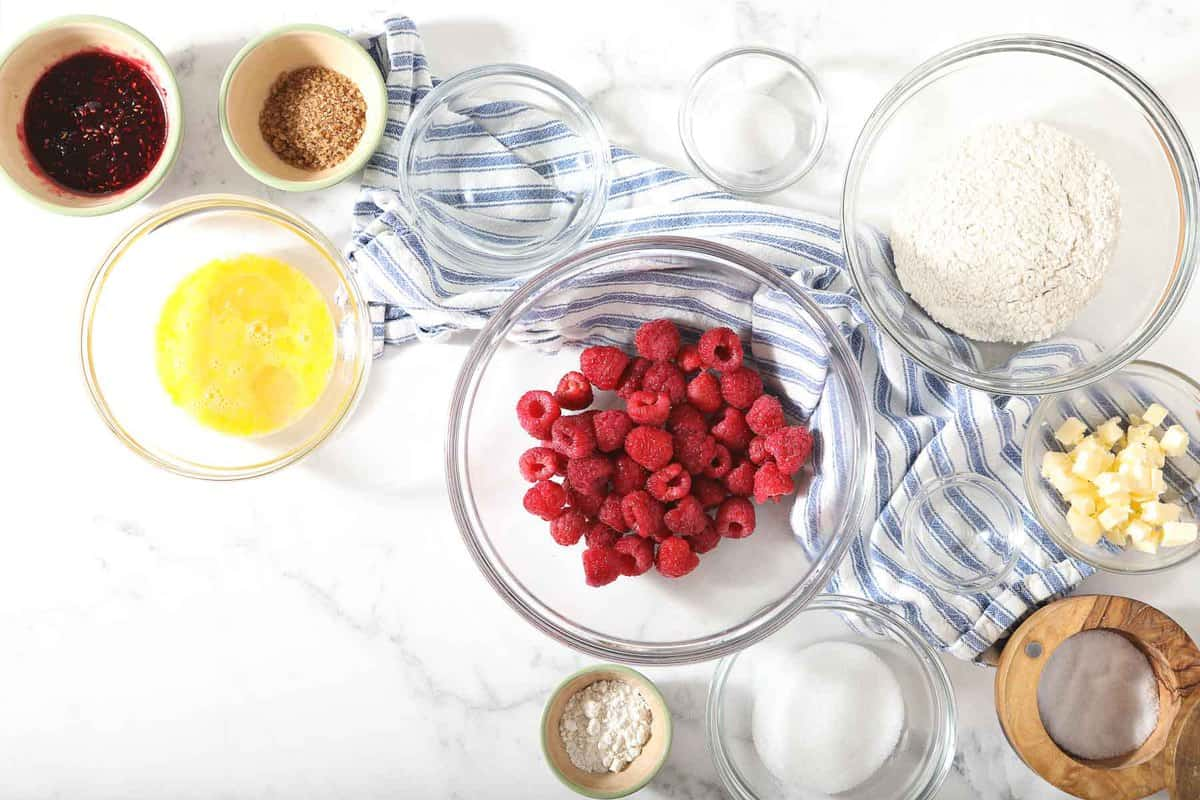 Ingredients for raspberry galette on a marble table.