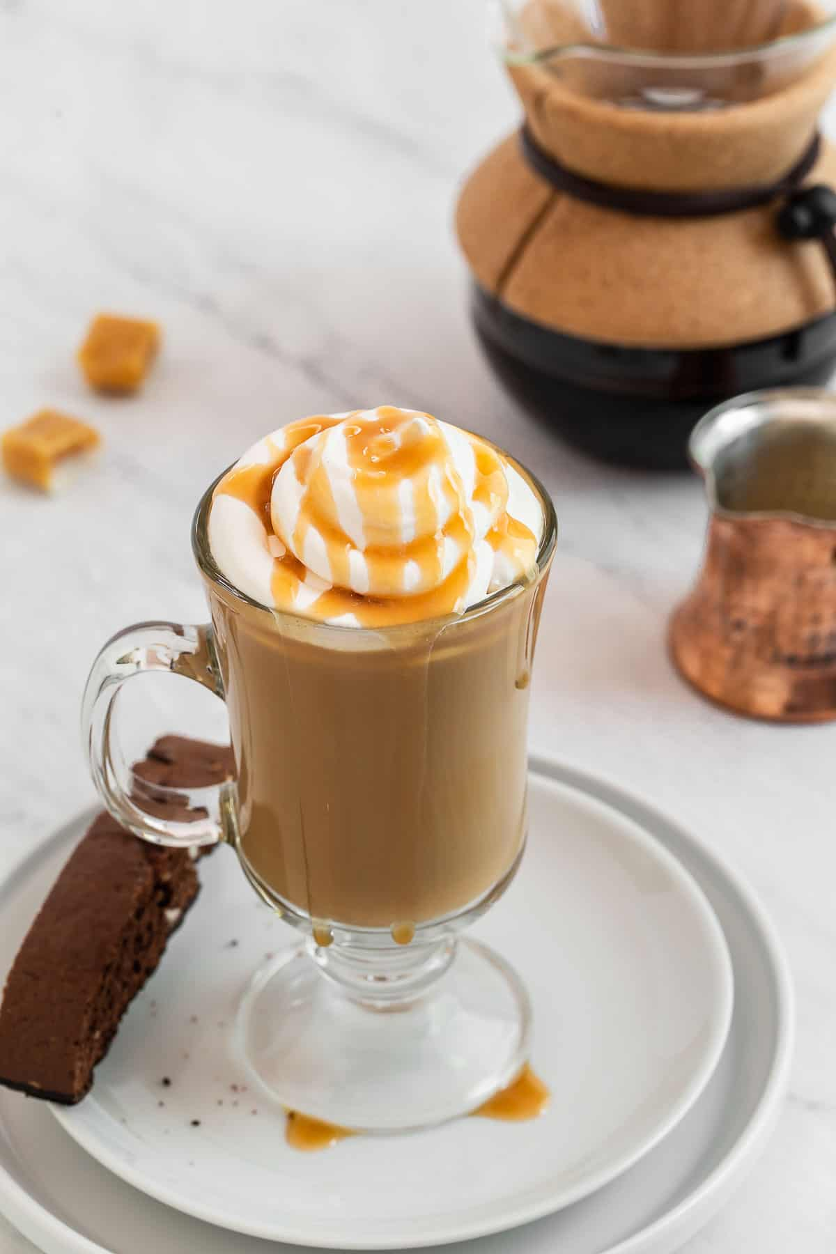 Caramel latte garnished with whipped cream and caramel drizzle.