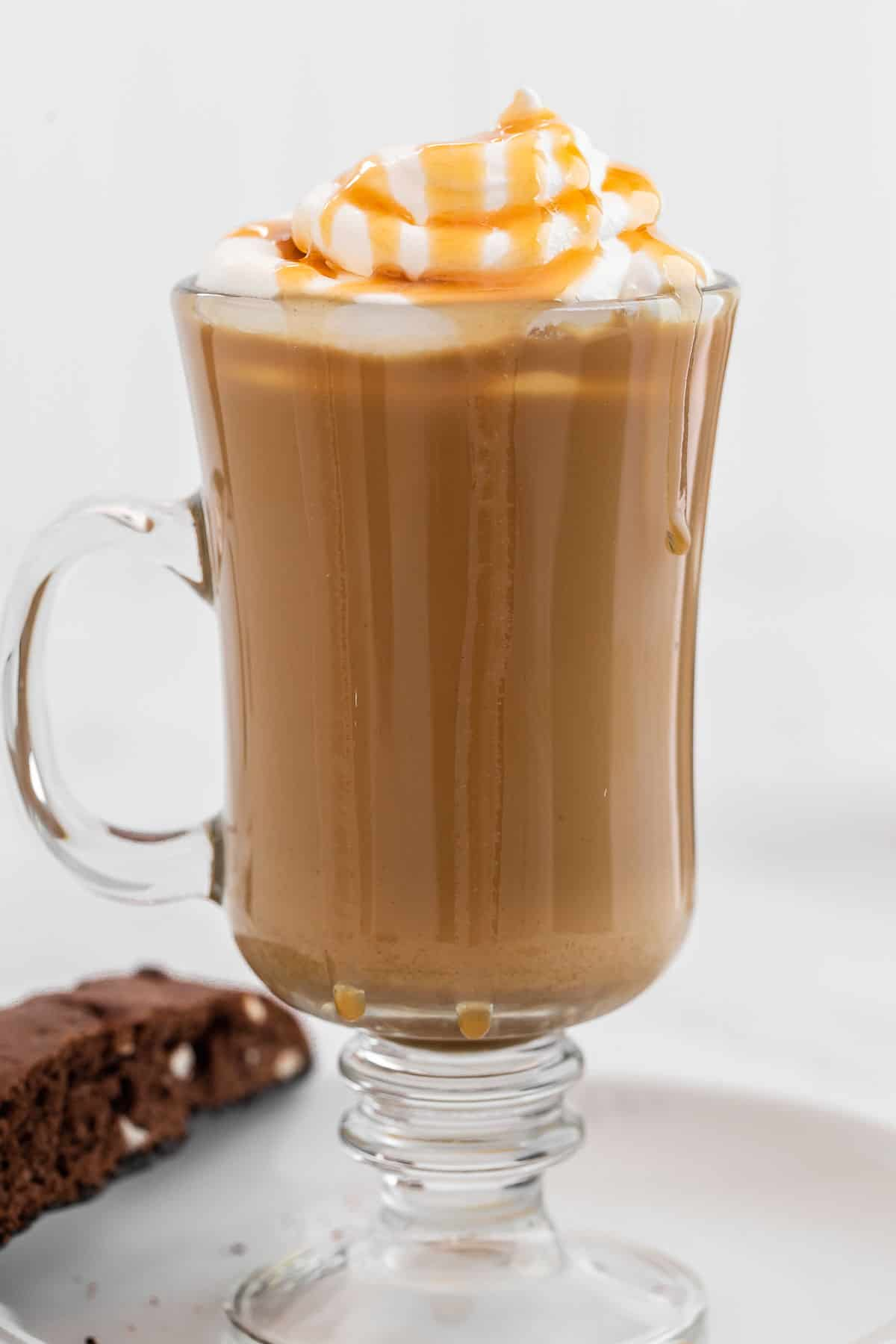 Close up of caramel latte in clear glass garnished with whipped cream and caramel.