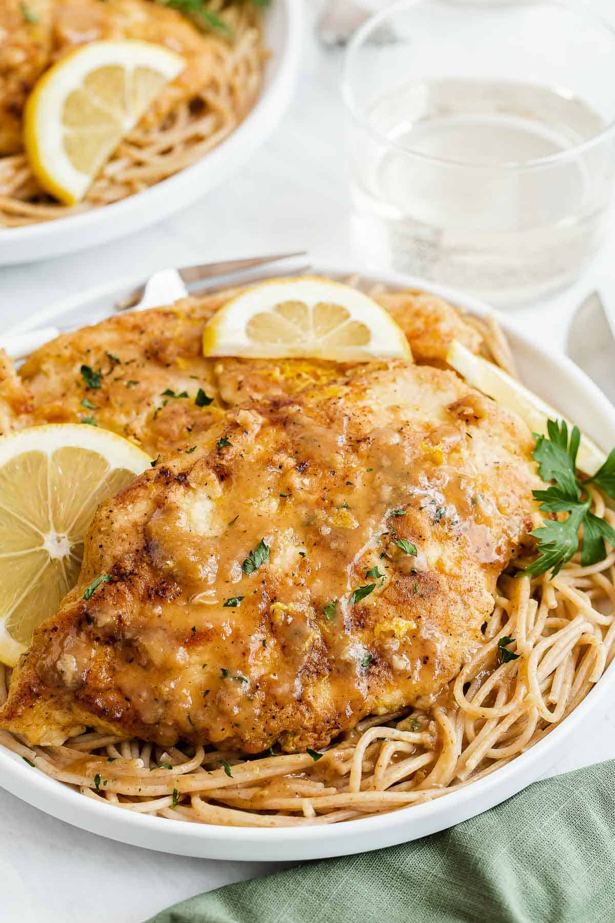 Saucy chicken cutlet over pasta on plate.
