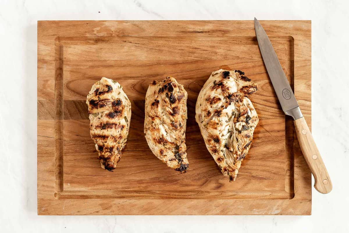 Three grilled chicken breasts on a wooden cutting board with knife.