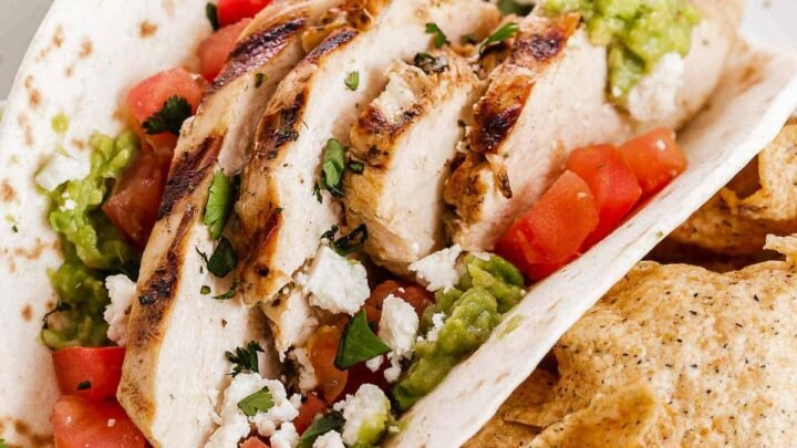 Soft tortilla with sliced chicken, guacamole and tomatoes.