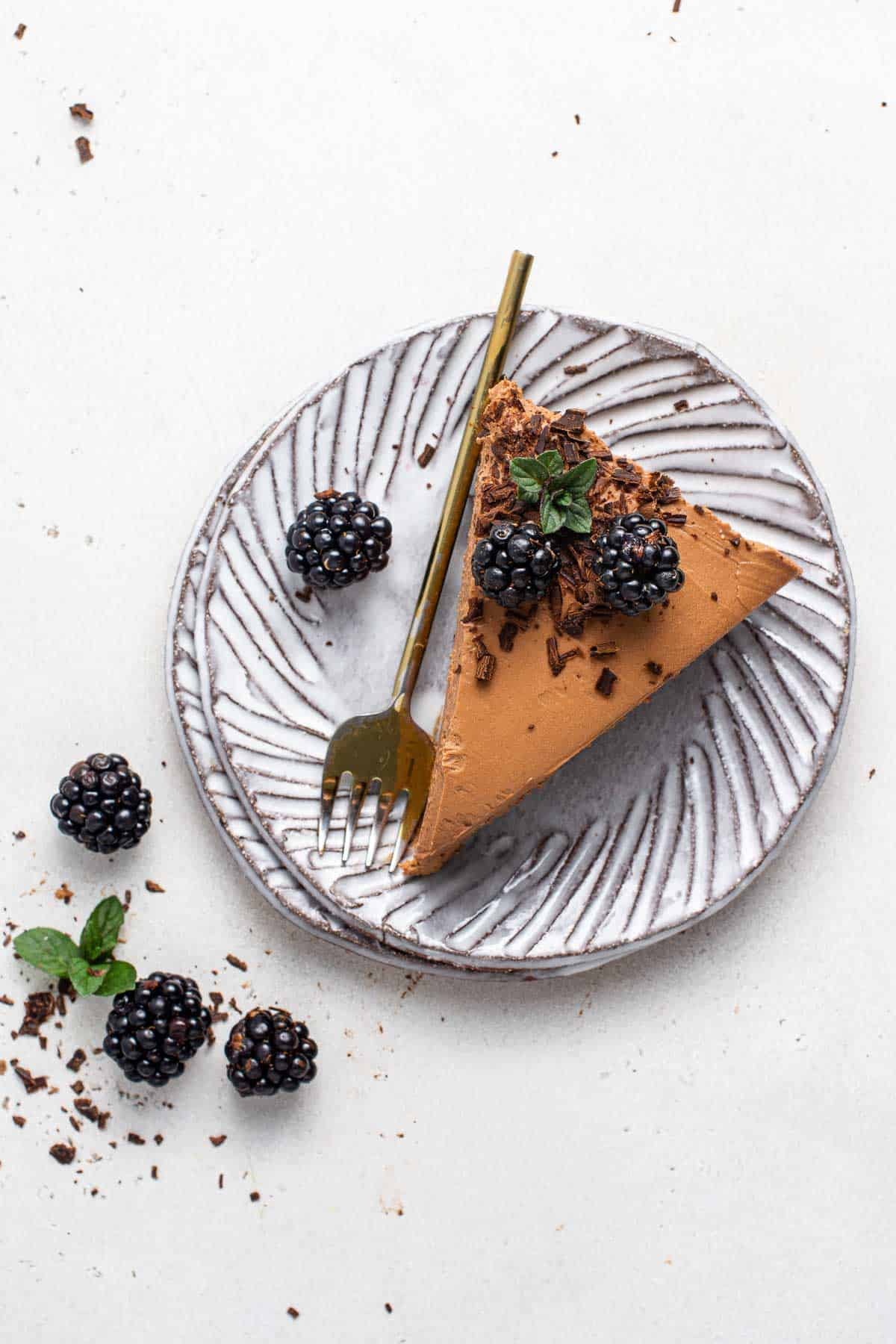 Slice of no bake chocolate cheesecake on a plate with blackberries.