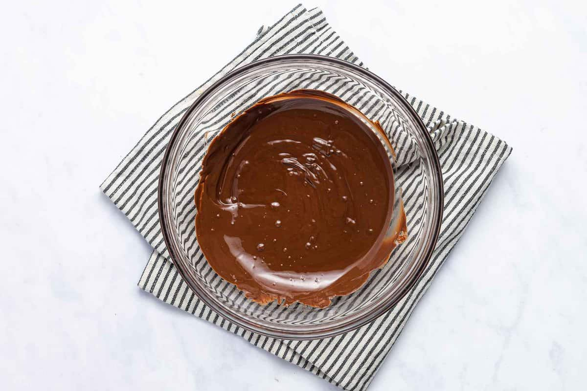 Melted chocolate in a clear bowl over a striped towel.