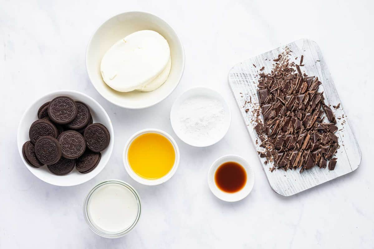 Ingredients for chocolate cheesecake on a white table.