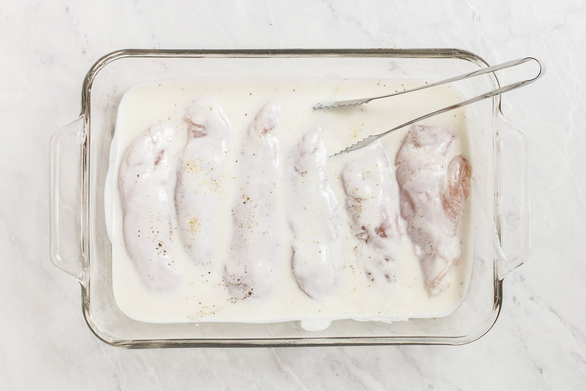 Chicken marinating in buttermilk with tongs.
