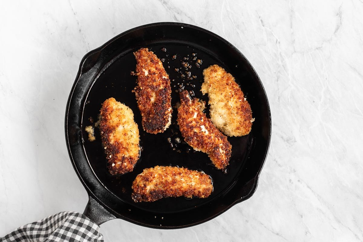 Chicken fingers in a cast iron skillet.