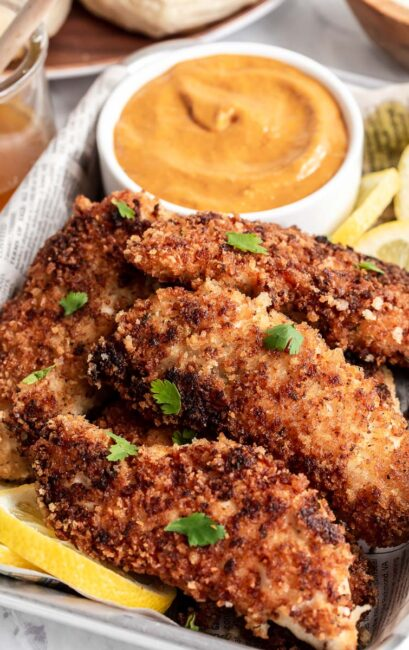 Pile of buttermilk chicken tenders with orange sauce in background.