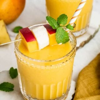 Two glasses of mango banana smoothie garnished with fruit and mint.