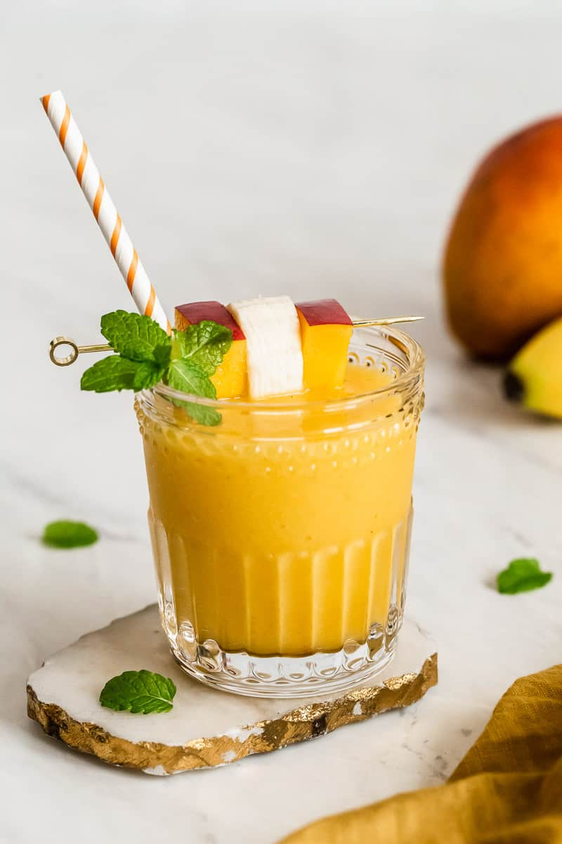 Mango banana smoothie in a glass with a straw and mint sprig.