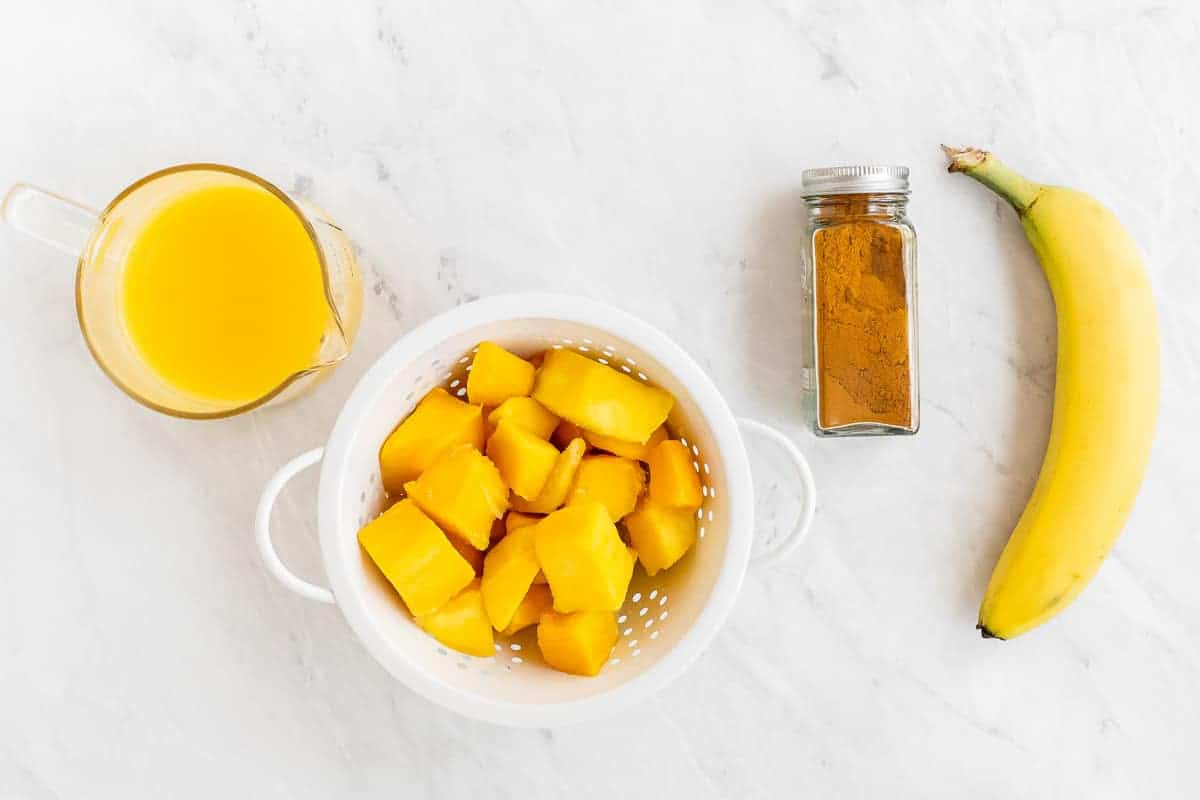 Orange juice, mango, turmeric and banana on white table.