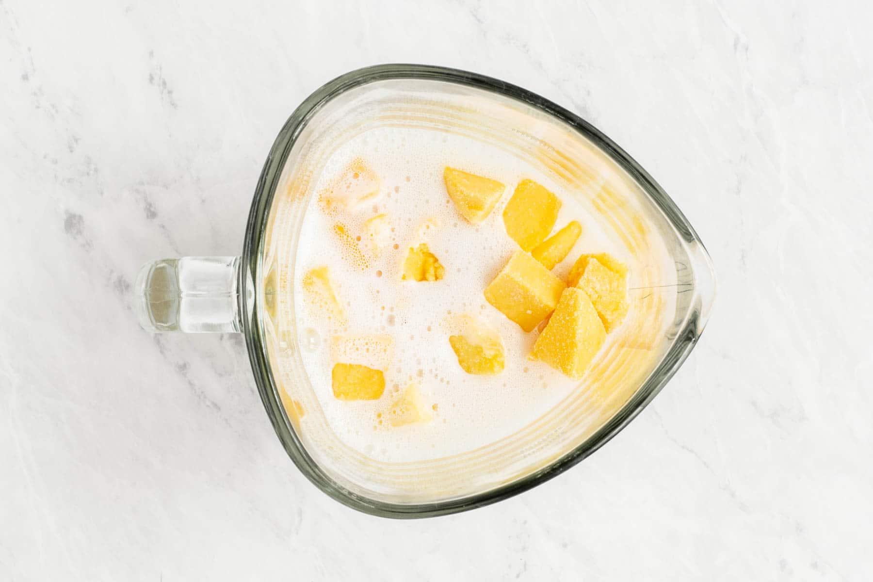 Mango chunks in blender with white liquid.