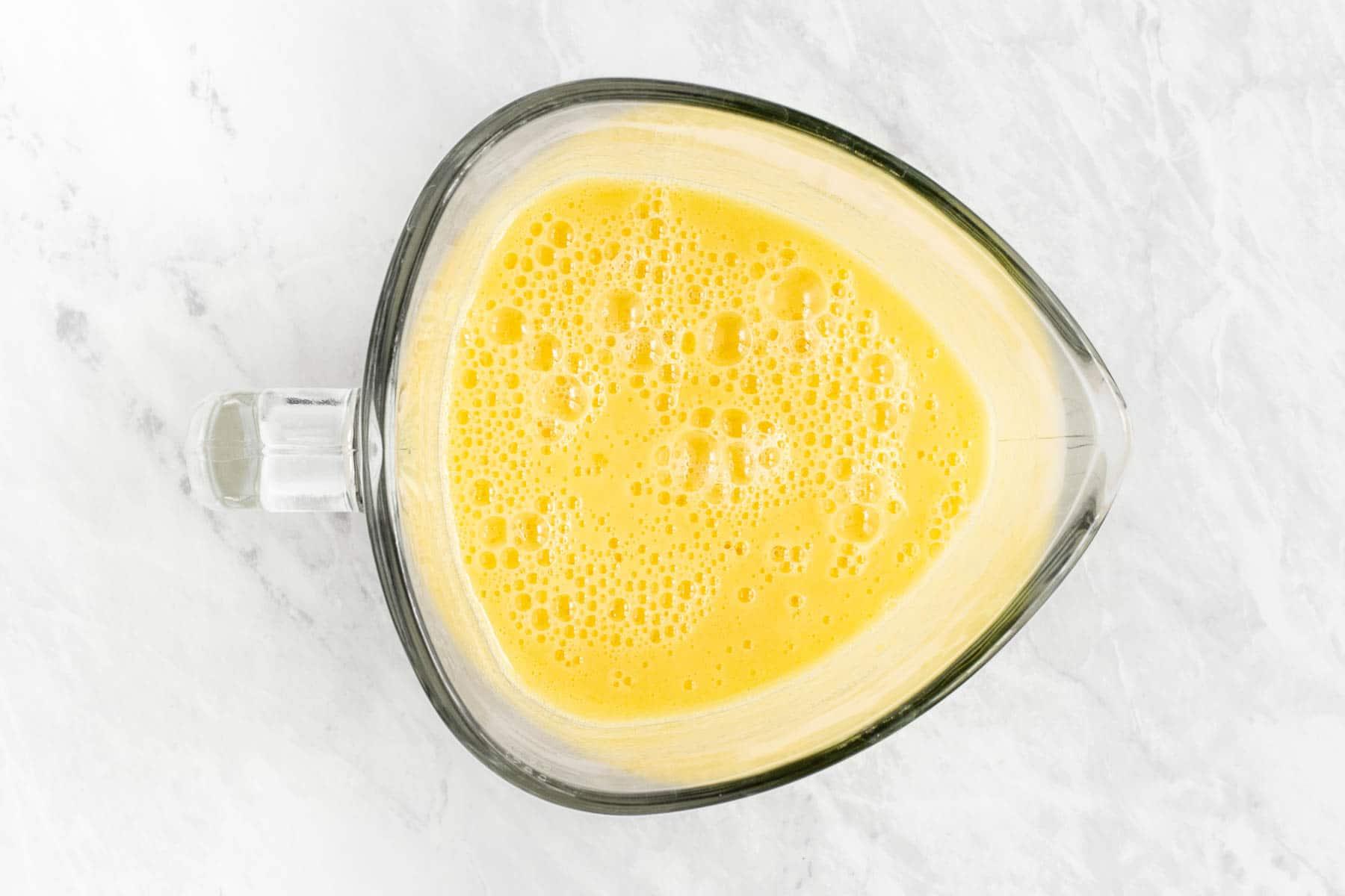 Blended mango lemonade in clear blender.