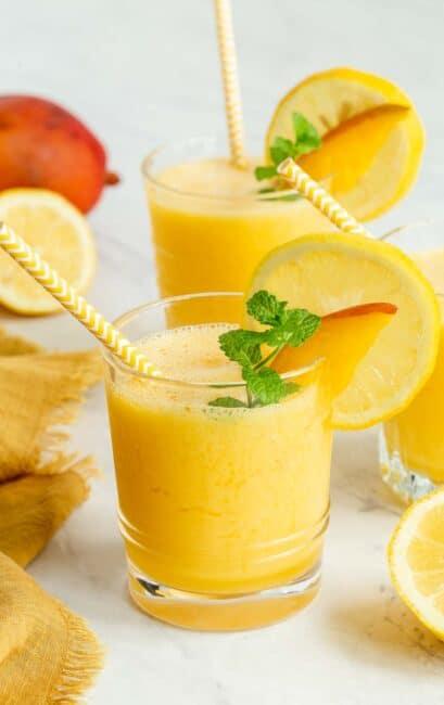 Two glasses of mango lemonade garnished with lemon slices.