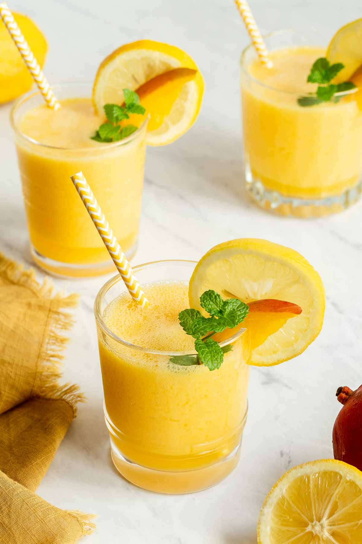 Three glasses of mango lemonade with straws and lemon rounds.