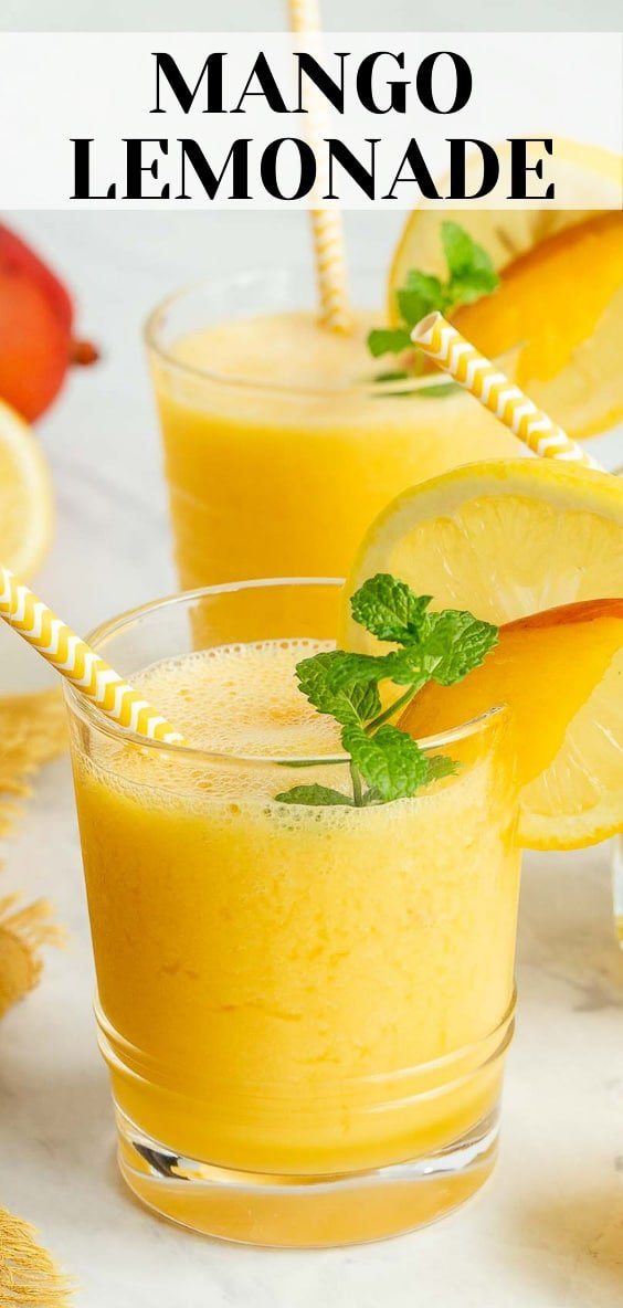 Two glasses of orange lemonade with mint and mango slices.