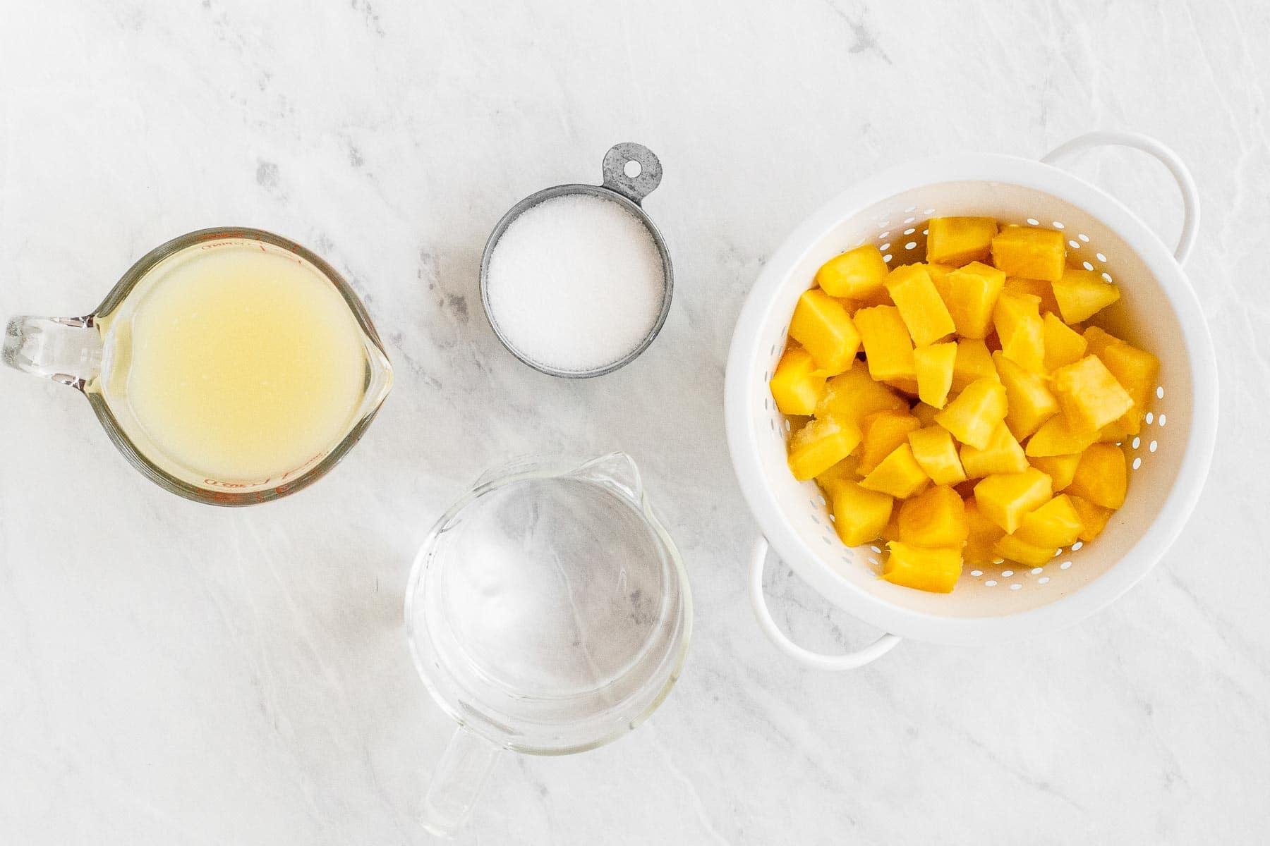 Ingredients for mango lemonade on white table.
