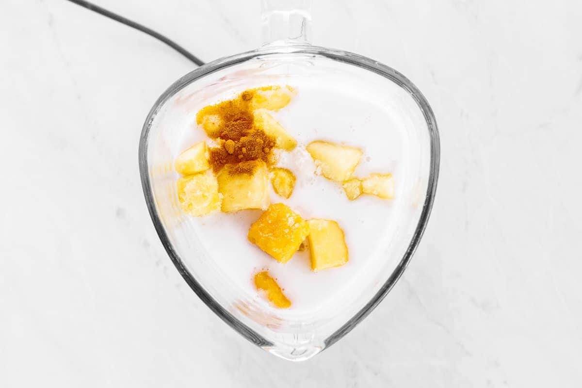 Mango smoothie ingredients piled in a blender.