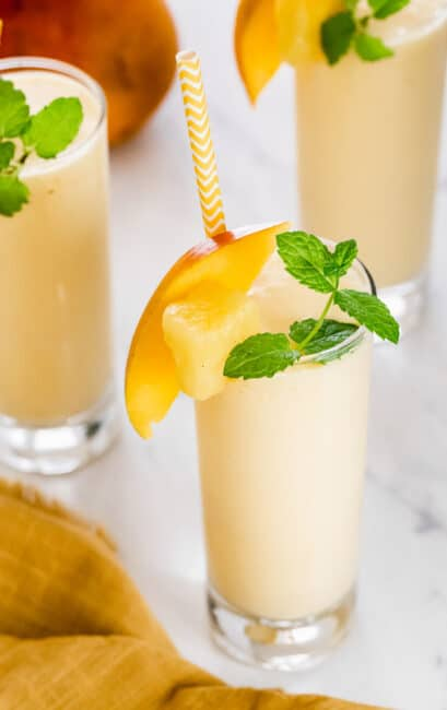 Mango pineapple smoothie in glasses garnished with mint.