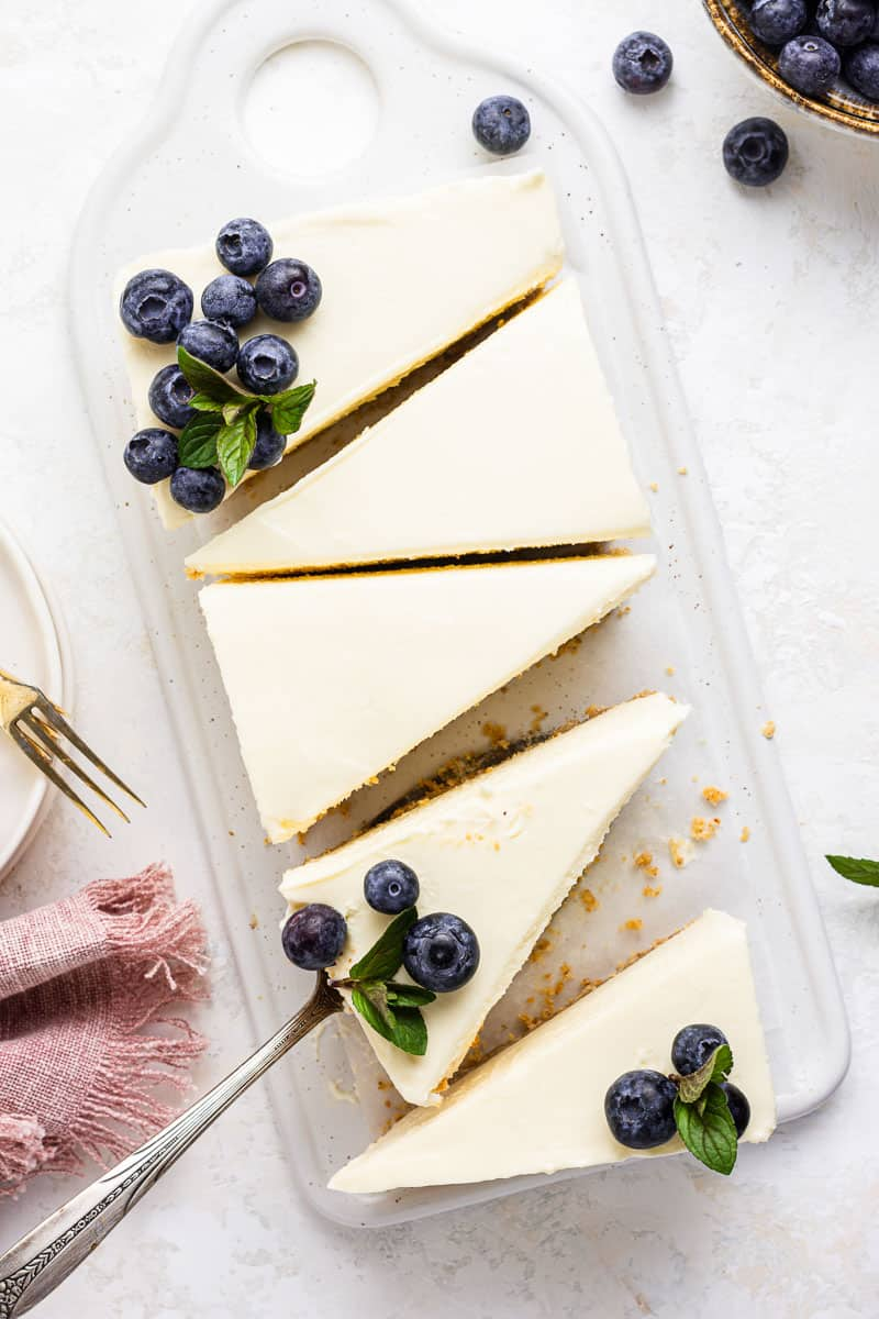 Rectangular cheesecake with fresh blueberries on top.