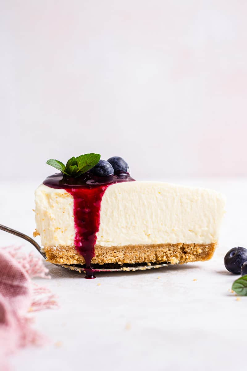 Slice of no bake blueberry cheesecake on a server.