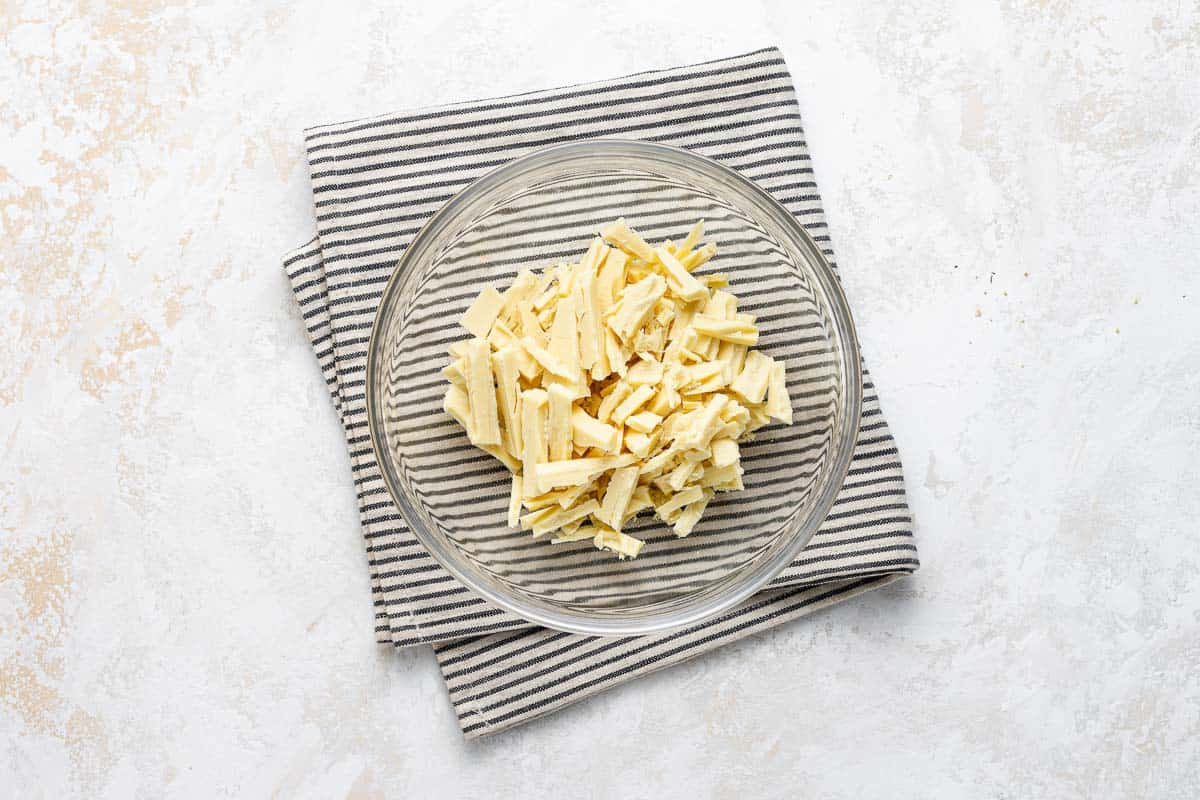 Chopped white chocolate in a clear bowl.