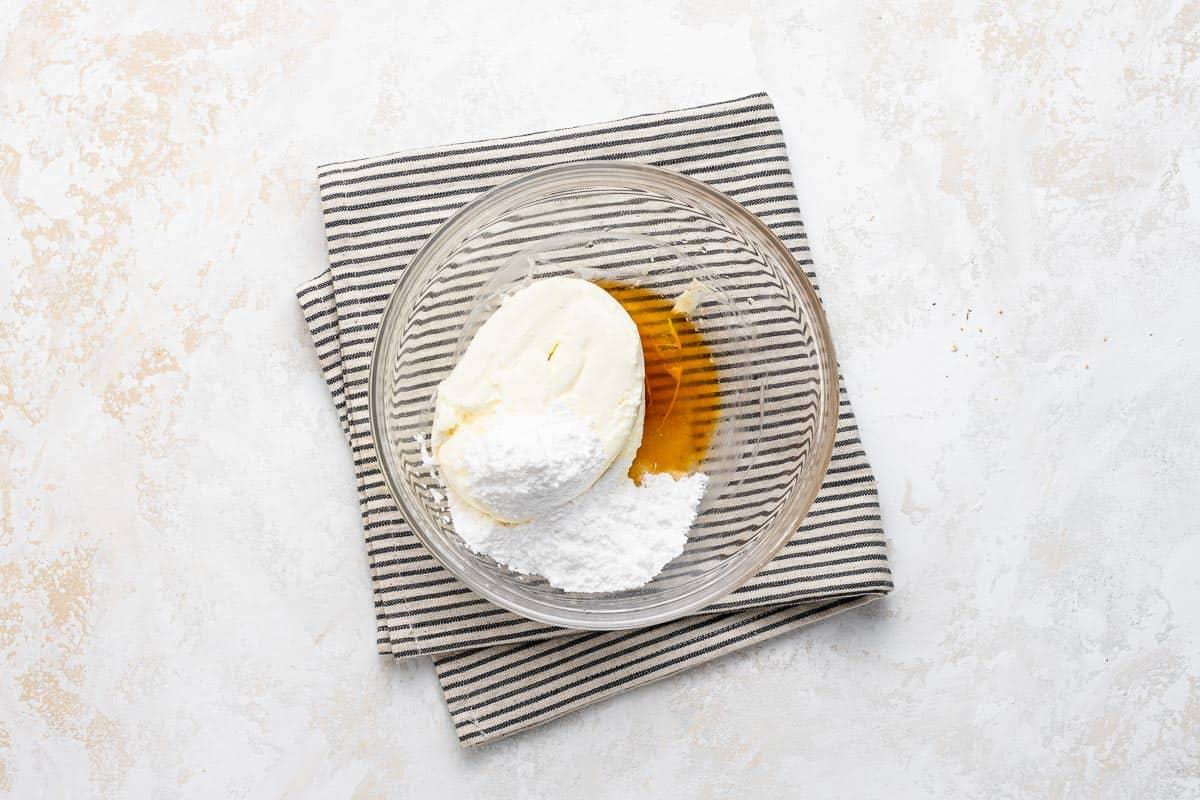Cream cheese, powdered sugar, and vanilla in a clear bowl.