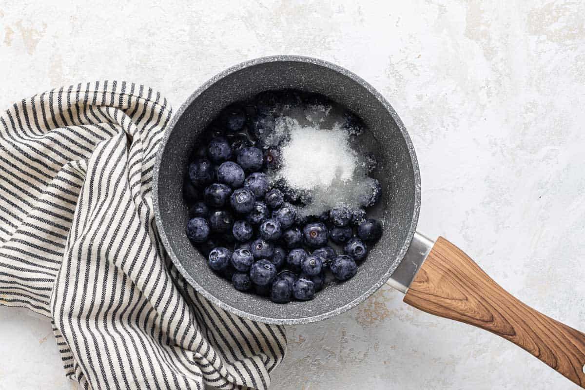 Blueberries and sugar in a small pot.
