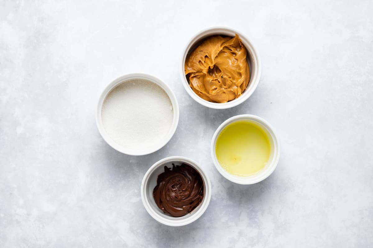 Ingredients for peanut butter Nutella cookies in little bowls.