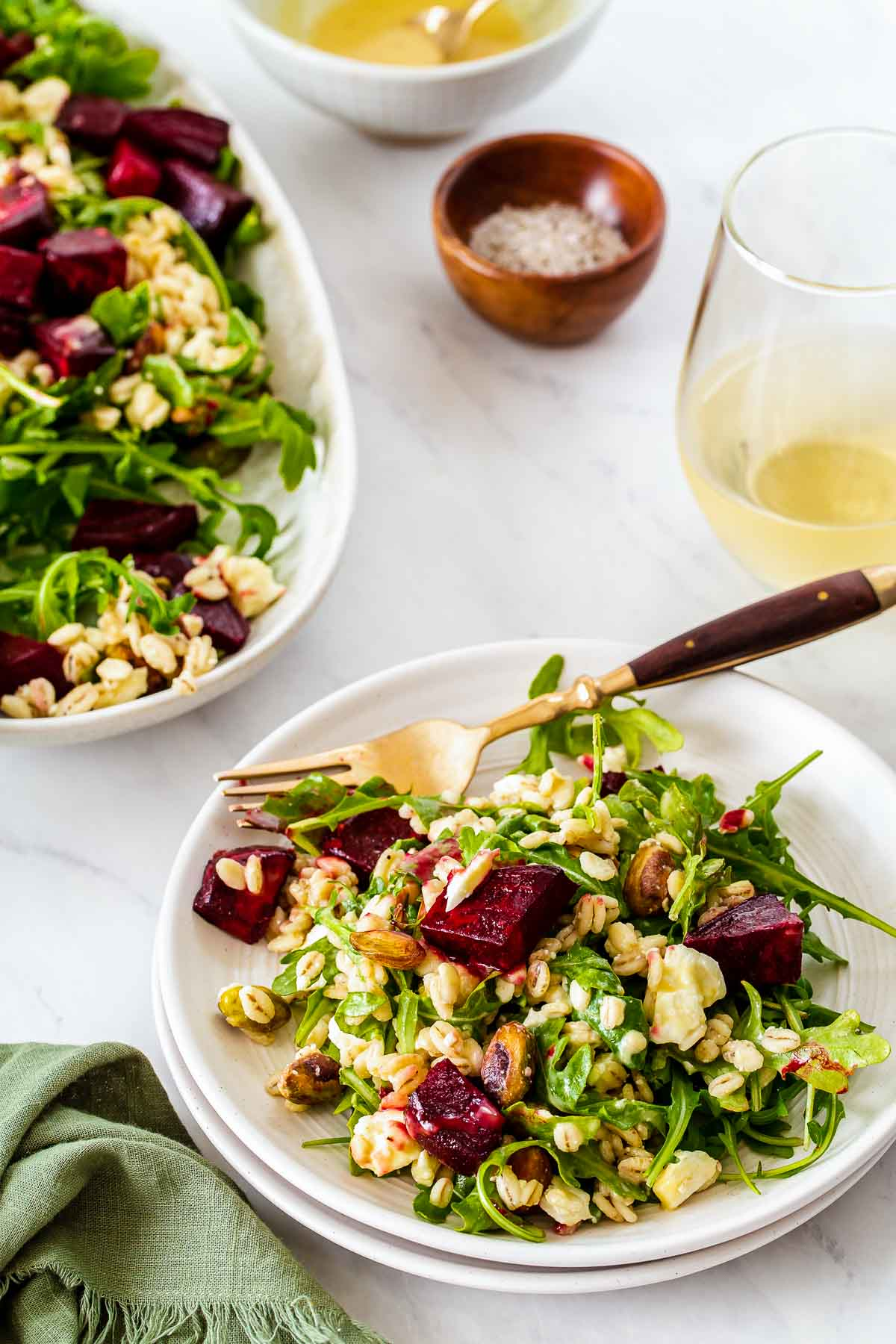 Two plates of beet salad with arugula and feta.