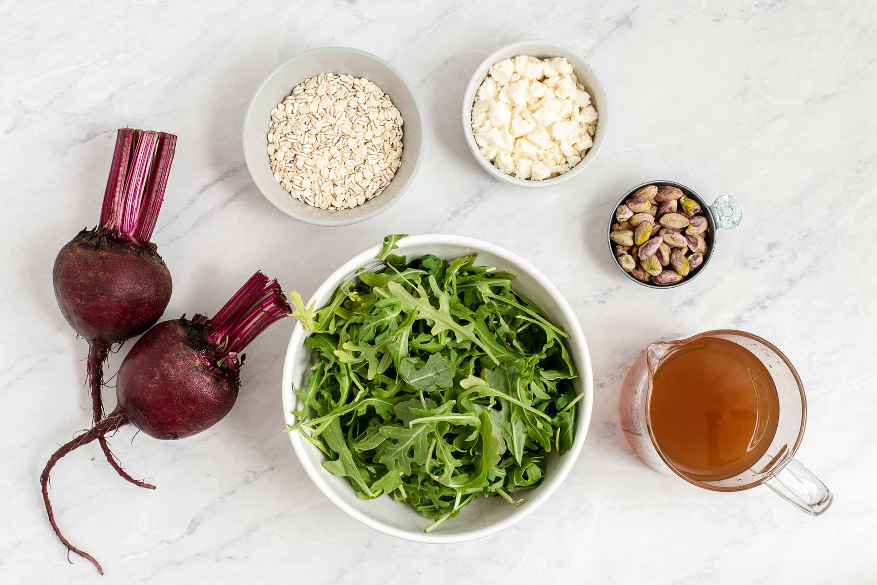 Ingredients for beetroot and feta salad on a white table.
