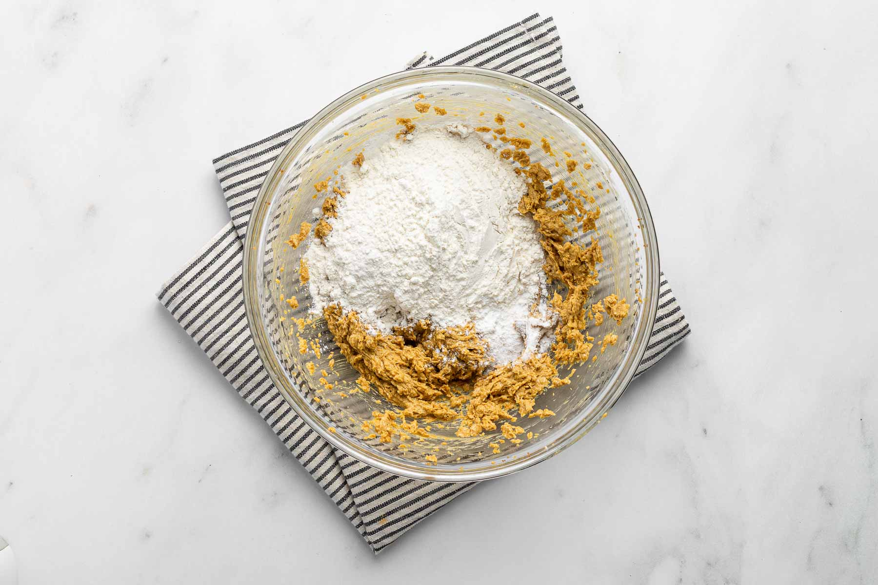 Flour over cookie dough in a glass bowl.
