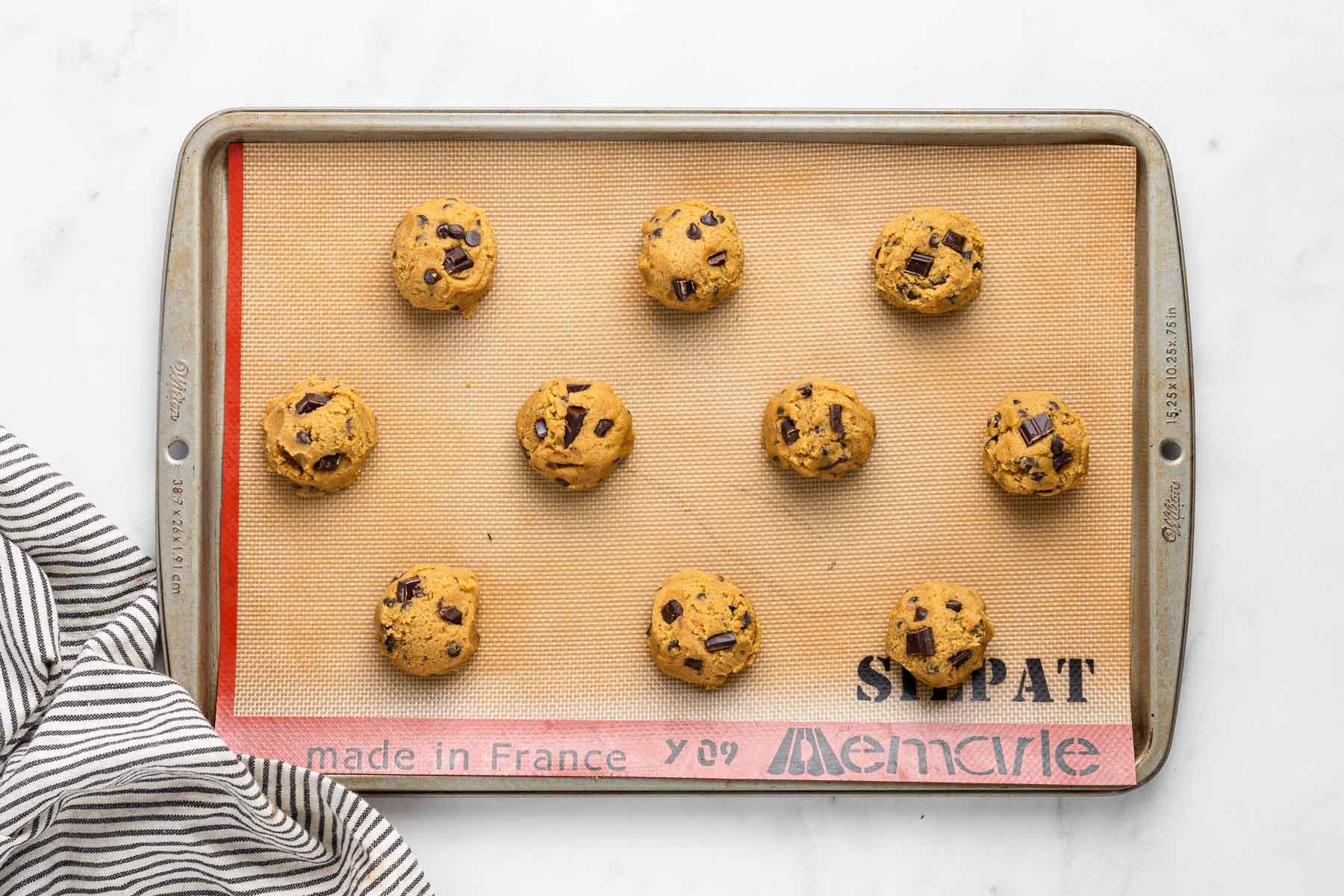 Ten cookie dough balls on a baking sheet.