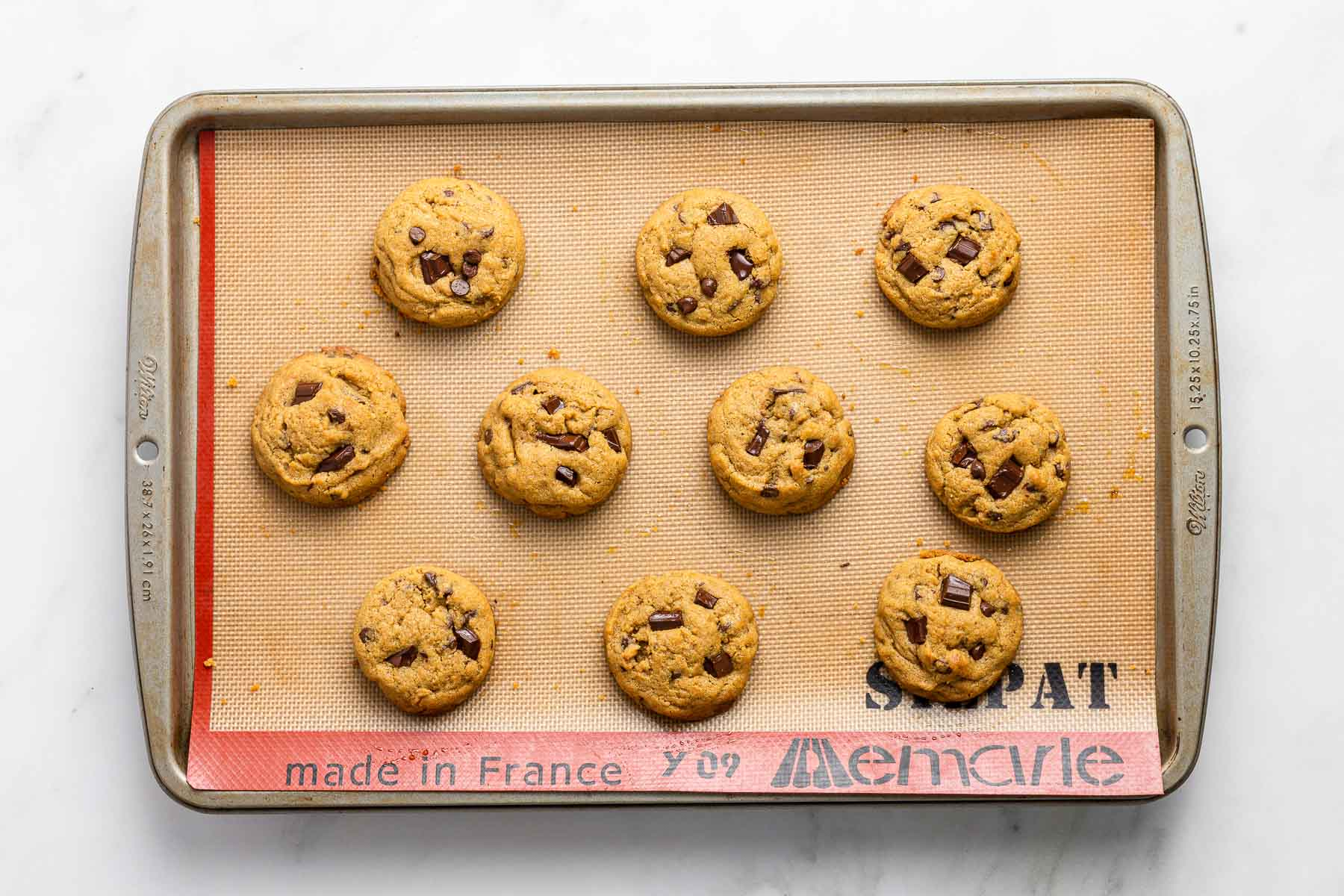 Ten brown sugar chocolate chip cookies baked on a baking sheet with a silicone mat.