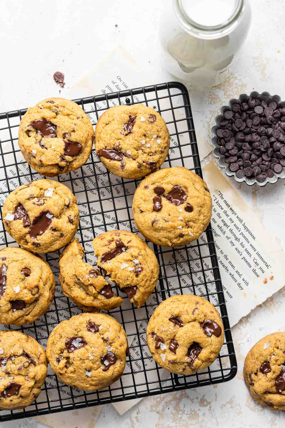 Cookies on a cool rack with milk and chocolate chips on the side.