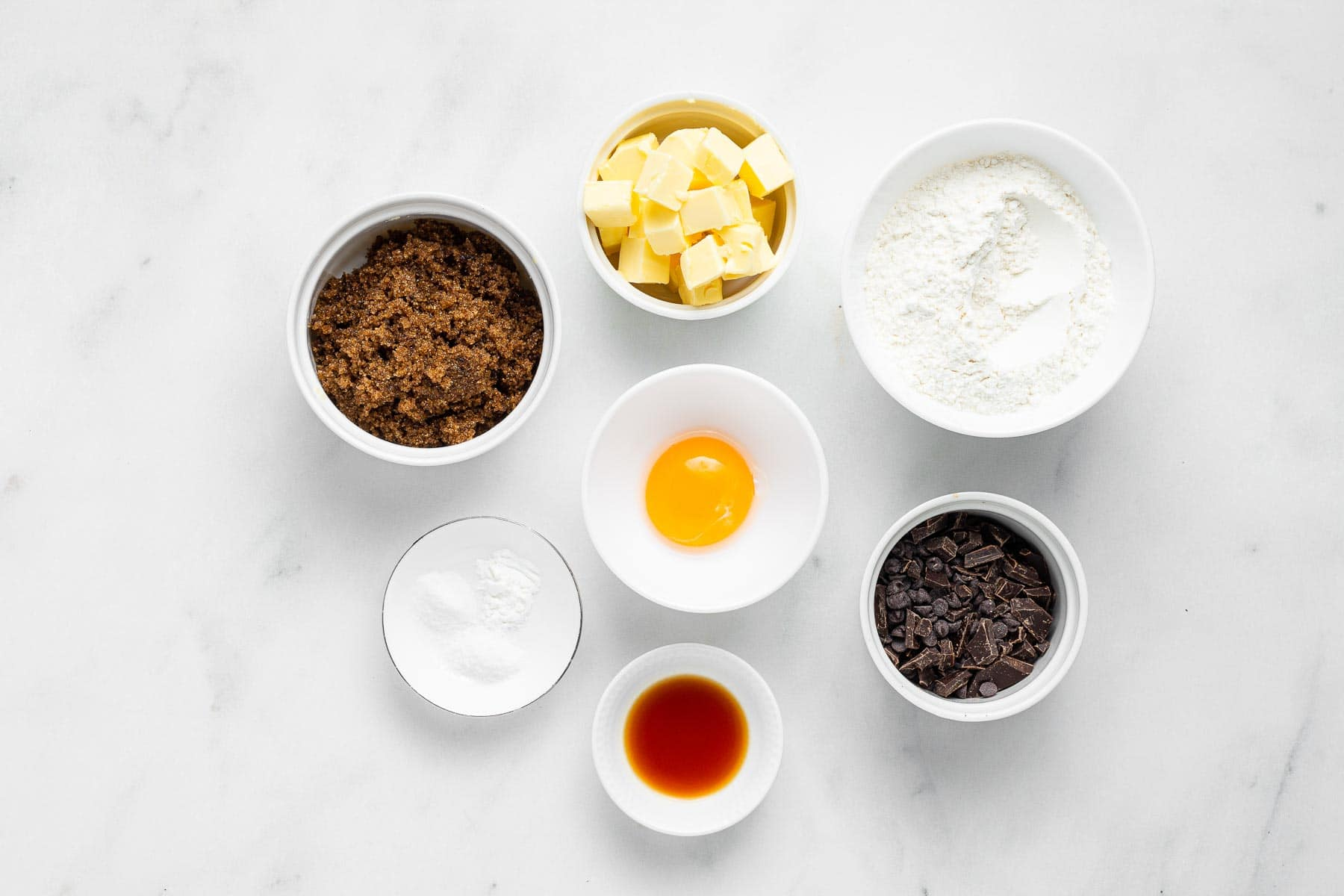 Ingredients for brown sugar chocolate chip cookies on white table in bowls.