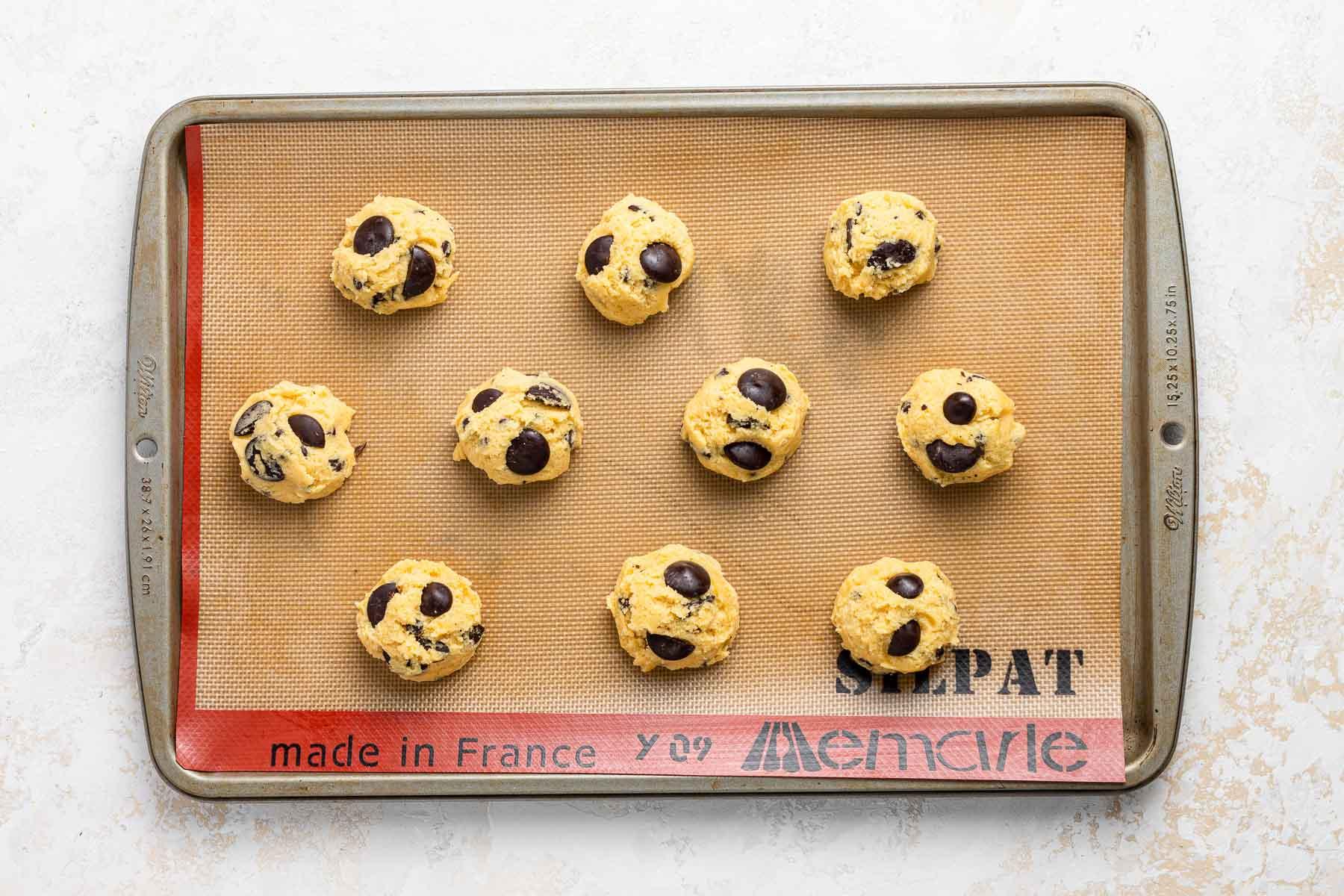 Ten balls of cookie dough on a baking sheet.