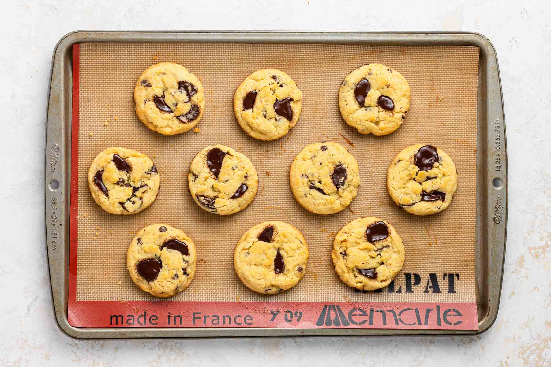 Baked chocolate chip cookies on a baking sheet.