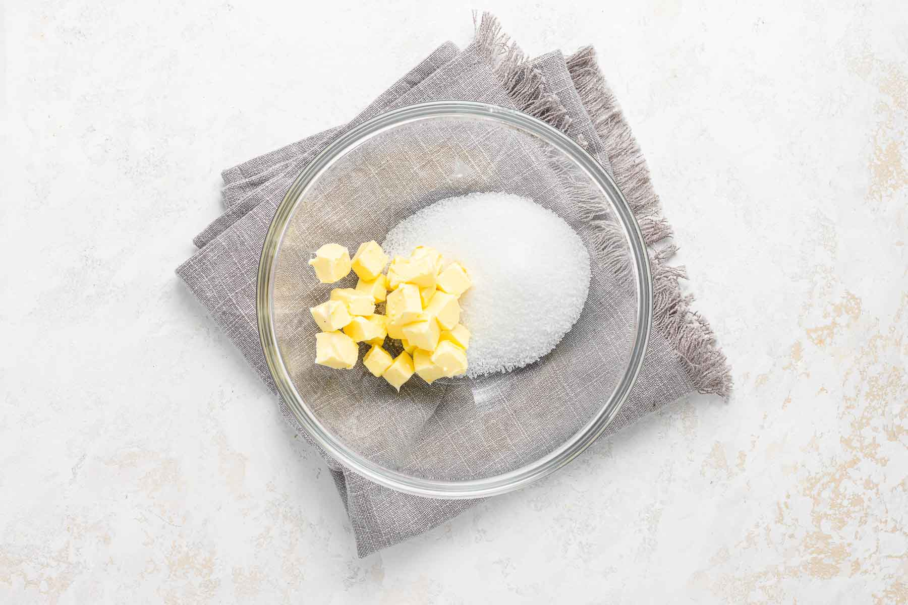 Cubed butter and sugar in a clear glass bowl.