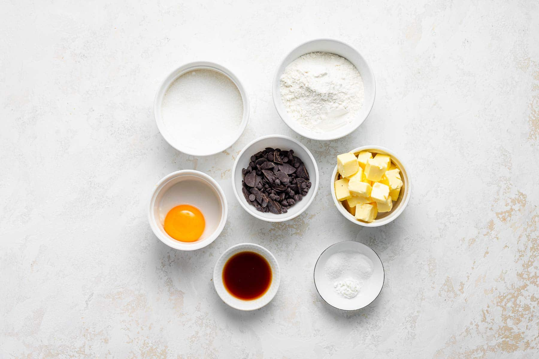 Ingredients for chocolate chip cookies without brown sugar on a white table.