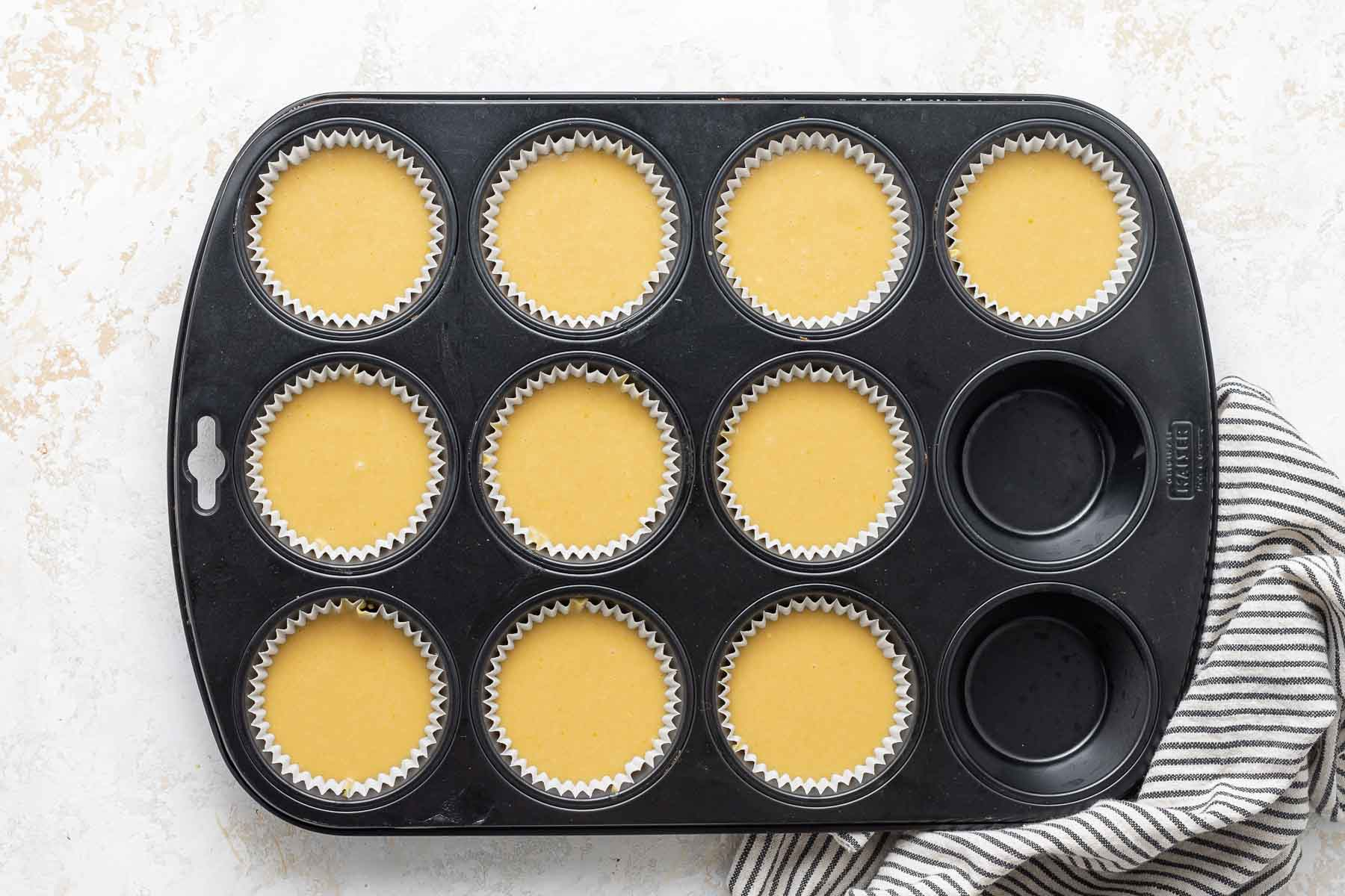 Yellow cupcake batter in muffin pan.