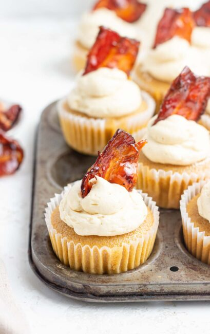 Close up of maple bacon cupcakes with bacon piece on top.