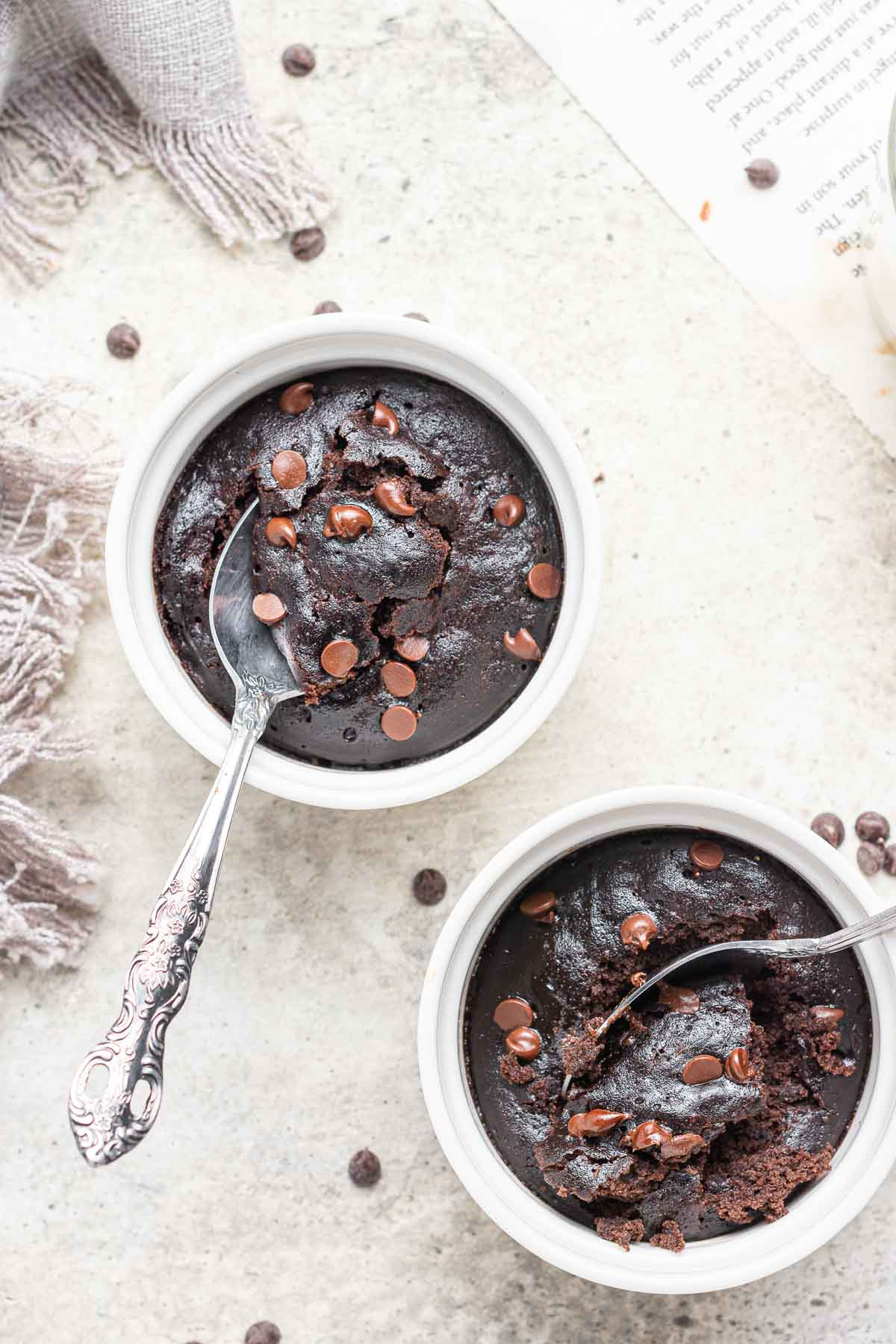 Two ramekins of microwave brownie pots with spoons.