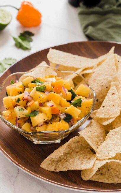 Mango salsa in clear dish with tortilla chips on side.